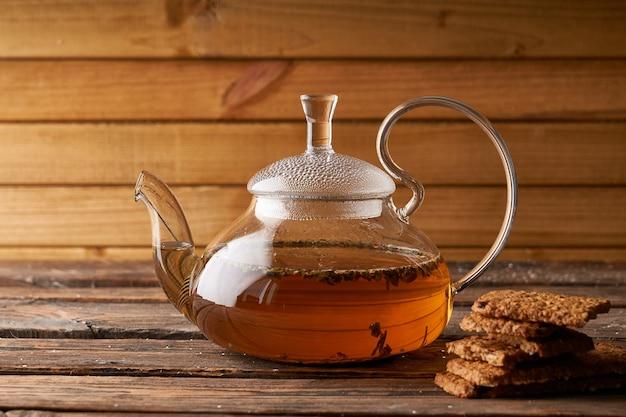 Théière avec thé chaud infusé et biscuits faits maison sur un fond en bois, confortable copy space