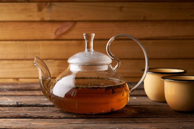 Théière avec thé chaud infusé sur un fond en bois, confortable