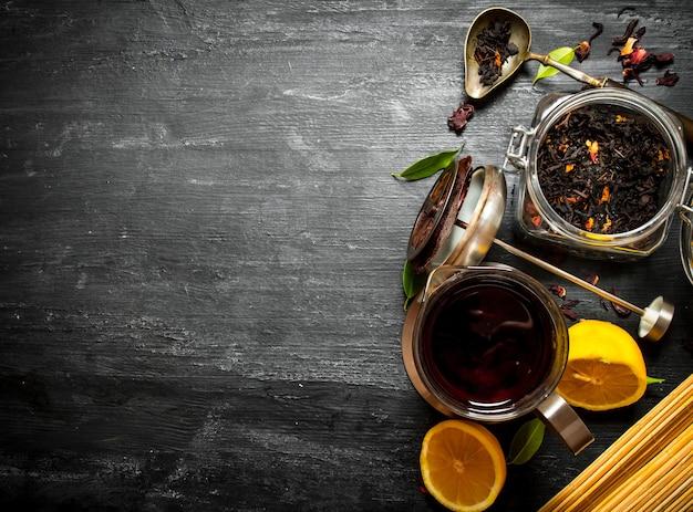 Théière avec thé et citron sur table en bois noir.