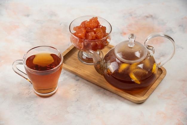 Théière de thé noir et confiture de coing sur plaque de bois.