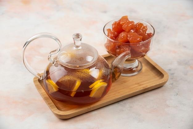 Théière de thé noir et confiture de coings sucrés sur plaque de bois.