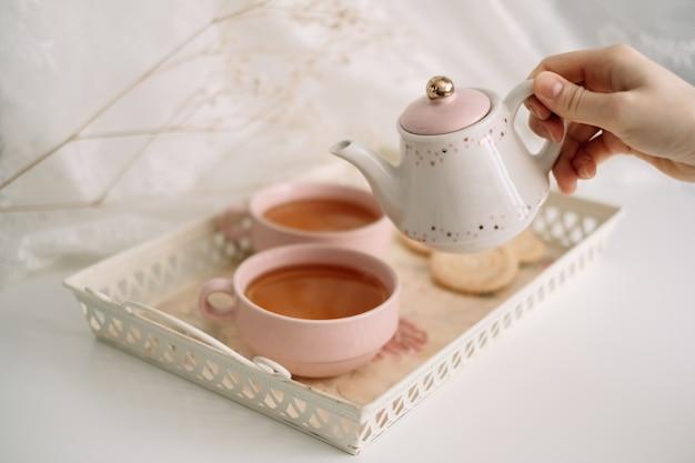 Théière avec thé et tasses sur un plateau