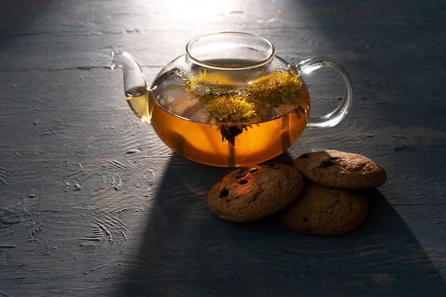 Théière transparente en verre avec tisane saine de pissenlits jaunes et biscuits à l'avoine avec raisins secs sur fond bleu en bois, éclairé par le soleil, discret.