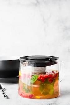 Théière en verre de canneberge, orange et menthe ou thé jaune sur une tasse noire isolée sur fond de marbre brillant. vue aérienne, espace copie. publicité pour le menu du café. menu du café. photo verticale.