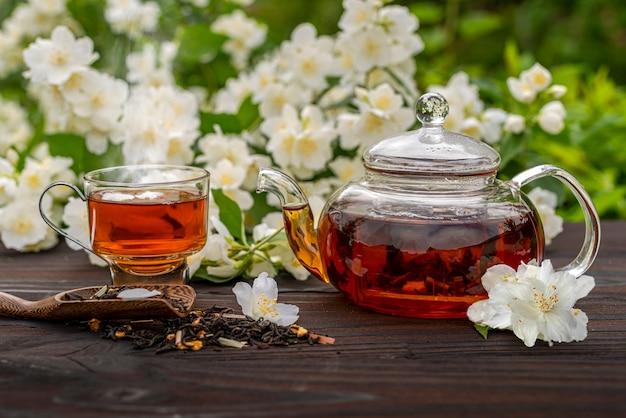 Théière en verre cuite à la vapeur avec du thé au jasmin une élégante tasse de thé parmi les buissons fleuris