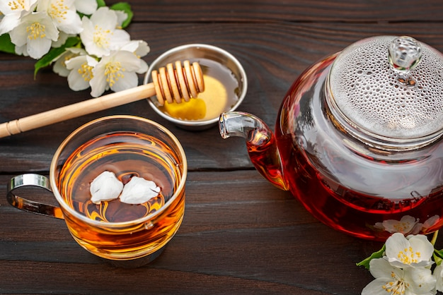 Théière en verre cuite à la vapeur élégante tasse avec thé et pétales miel louche