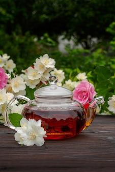 Théière en verre cuite à la vapeur sur une table en bois parmi des buissons fleuris de roses et de jasmin