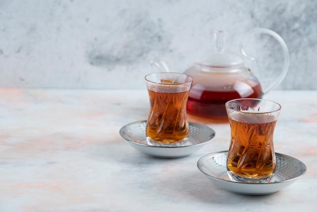 Théière et verre deux thé en verre sur une surface blanche