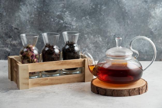 Une théière en verre avec du thé sur planche de bois.