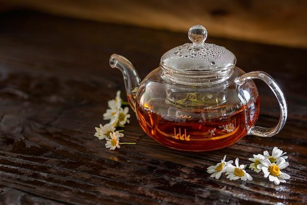 Théière en verre fumante avec thé à la camomille sur une table en bois humide.