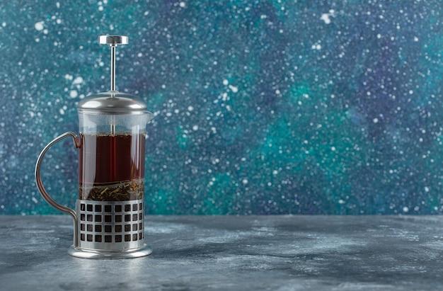 Théière en verre pleine de thé frais parfumé.