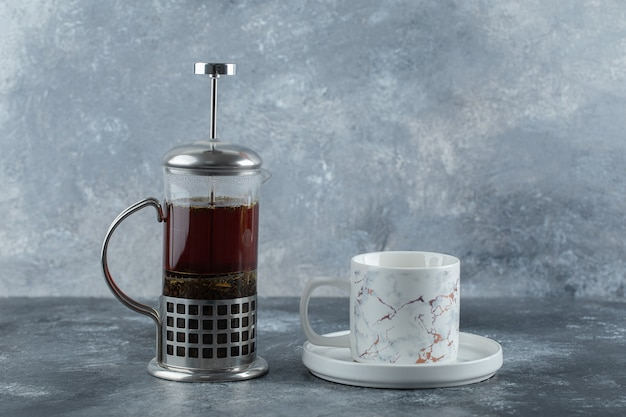 Théière en verre avec tasse sur table grise.
