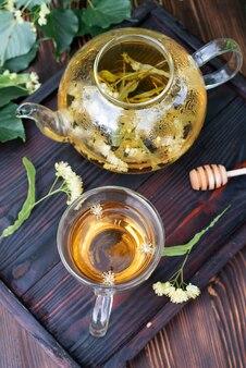 Théière en verre et une tasse de thé au tilleul sur un plateau en bois foncé sur la table, tisane saine, gros plan.