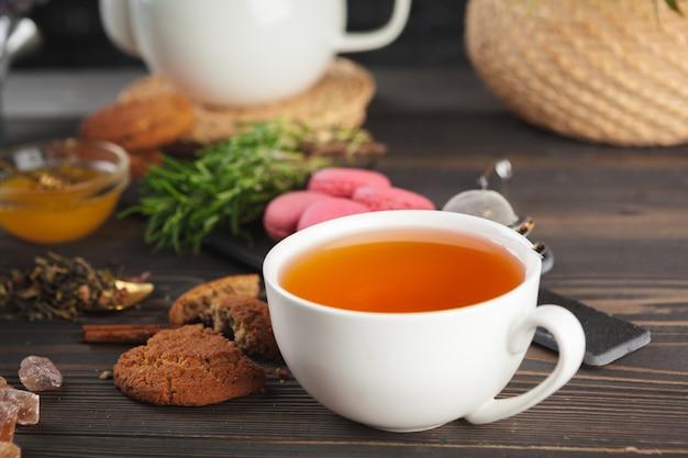 Théière en verre avec une tasse de thé noir sur une table en bois