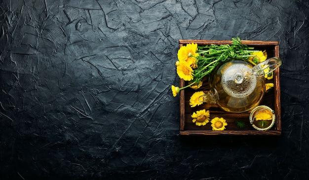 Théière en verre avec thé aux fleurs de chrysanthème. thé aux fleurs. phytothérapie. phytothérapie et homéopathie. tisane. espace copie