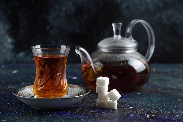 Théière et verre de thé avec du sucre