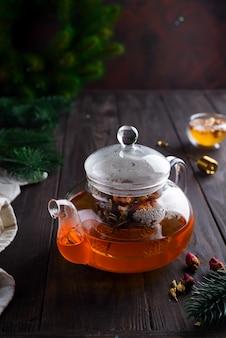 Théière en verre avec tisane fraîchement préparée et miel sur un fond en bois.