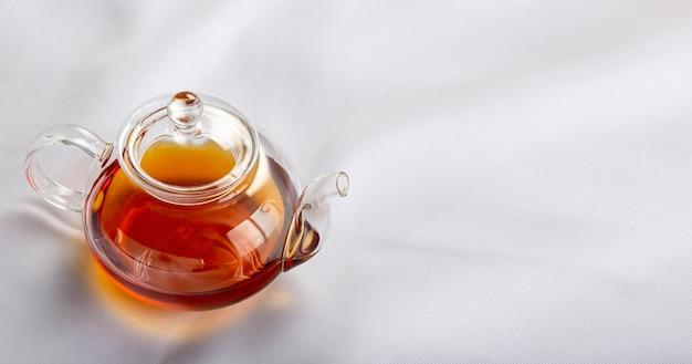 Théière en verre transparent avec du thé sur une nappe blanche.