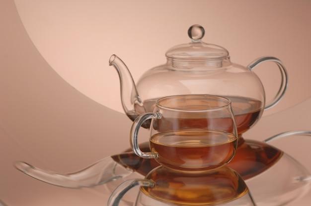 Théière en verre transparent et tasse de thé sur la surface réfléchissante
