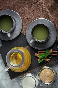 Théière en verre transparent avec thé aux agrumes et tasses