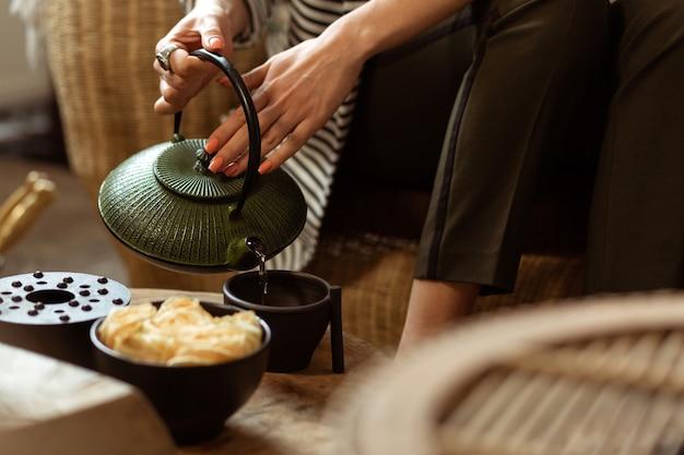 Théière verte authentique. dame tranquille et douce remplissant une tasse en céramique noire de thé chaud en attendant son tour