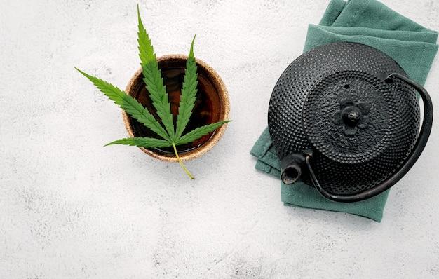 Théière vintage avec tisane de cannabis et feuilles de marijuana fraîches installées sur du béton.