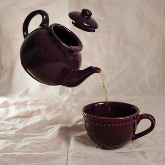 Une théière violette et une tasse de thé violette sur fond blanc.