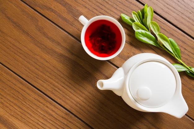 Théière vue du dessus avec tasse de thé et feuilles