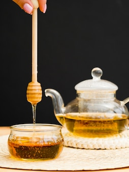 Théière vue de face et main tenant une louche à miel sur un bocal