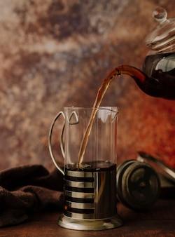 Théière vue de face versant du thé dans un moulin