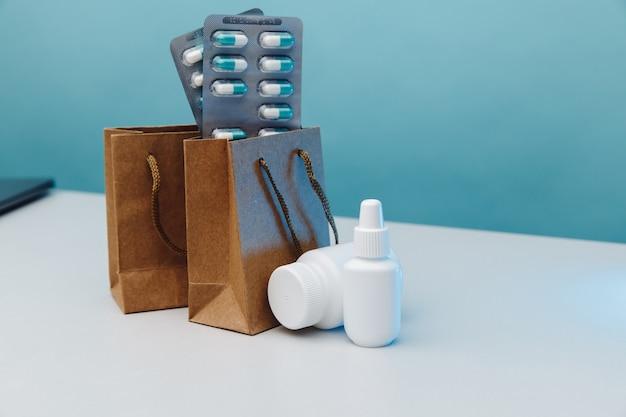 Thème d'achat en ligne. sacs en papier avec des contenants médicaux blancs et des pilules sur fond bleu.