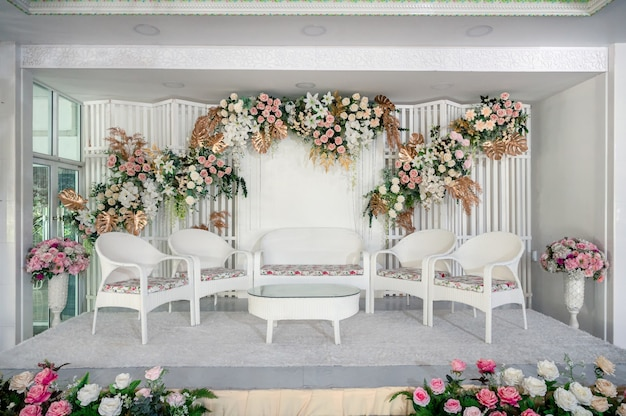 Thème blanc de la décoration de scène de mariage avec des fleurs colorées et une chaise pour invité en mariage traditionnel asiatique
