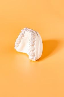 Thème dentaire orthodontique de plateau de dent individuelle de gros plan. en main bretelles invisibles