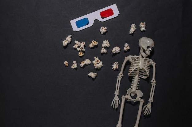 Thème d'halloween. squelette, pop-corn et lunettes 3d sur fond noir. film d'horreur. vue de dessus