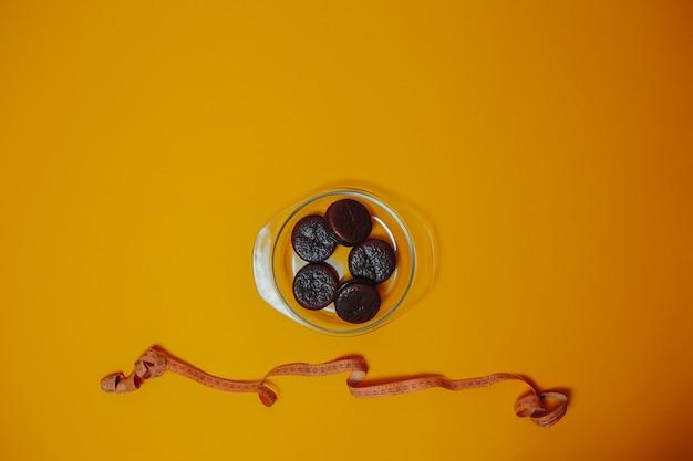 Thème de régime et de perte de poids. gâteaux au chocolat sur la plaque avec un ruban à mesurer.