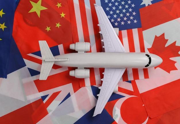 Thème de voyage avia. la figure d'un avion de ligne sur le fond de nombreux drapeaux de pays