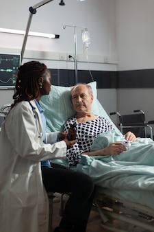 Thérapeute afro-américain dans la chambre d'hôpital discutant du traitement