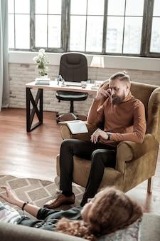 Thérapeute barbu. vue de dessus d'un thérapeute barbu professionnel écoutant son client et prenant des notes