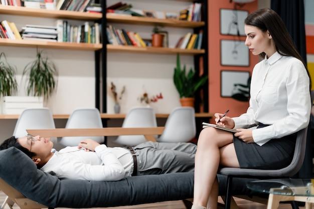 Une thérapeute consulte une employée de bureau sur un canapé