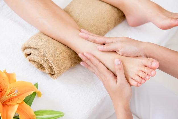 Thérapeute donnant un massage relaxant traditionnel des pieds à une femme dans un spa