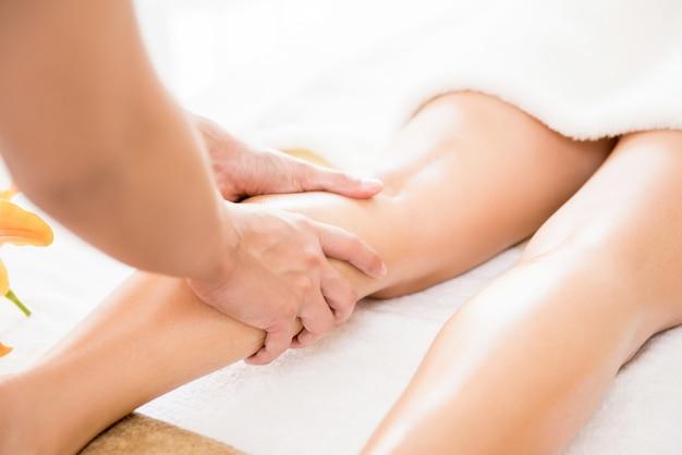 Thérapeute donnant un massage thaïlandais aux jambes à l'huile à une femme dans un spa