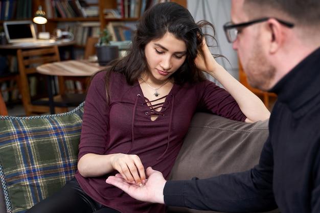 Thérapeute donnant des pilules à une patiente pendant une séance de thérapie