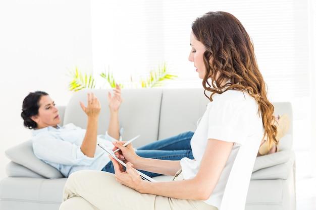 Thérapeute à l'écoute de son patient et prendre des notes
