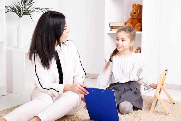 Thérapeute féminine travaillant avec un enfant ayant un problème de prononciation dans le cabinet blanc.