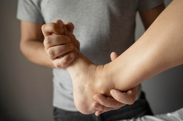 Thérapeute gros plan tenant le pied du patient