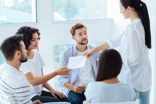 Thérapeute de groupe amicale professionnelle tenant des feuilles de papier et les donnant à ses patients tout en se préparant à commencer une nouvelle activité psychologique