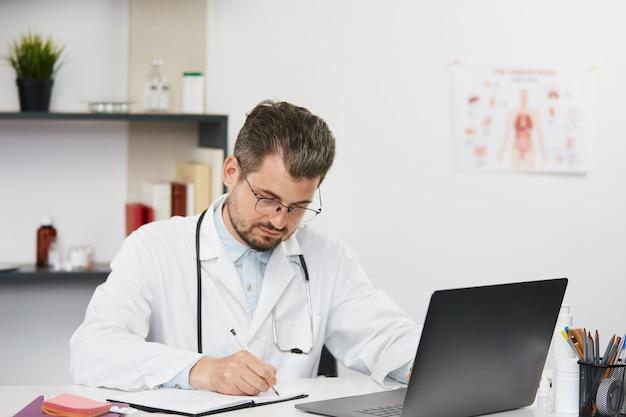 Thérapeute masculin barbu en robe médicale blanche et lunettes assis dans le cabinet médical avec stéthoscope, chirurgien analysant les documents des patients à l'aide de pc