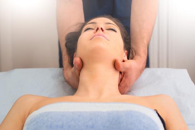 Thérapeute massant le cou de la femme dans le par un professionnel
