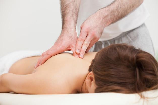 Thérapeute masser le haut du dos de la femme en se tenant debout
