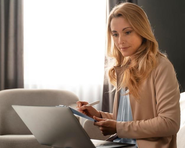 Thérapeute mid shot prenant des notes avec un ordinateur portable sur les genoux